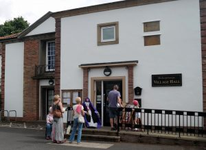 Visitors outside the Village Hall with 'Archbishop Maclagan'.